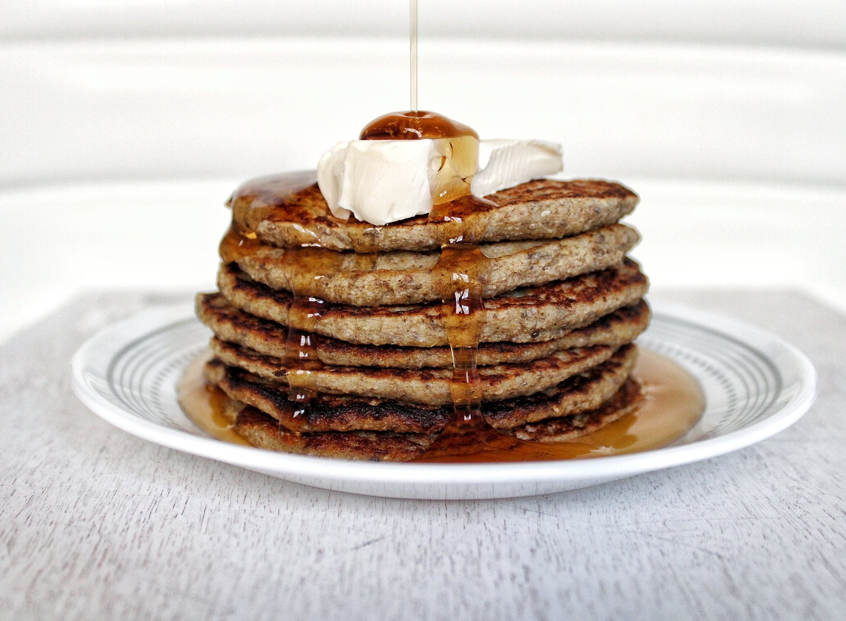 Stack of gluten-free, vegan banana pancakes with a drizzle of syrup and vegan butter
