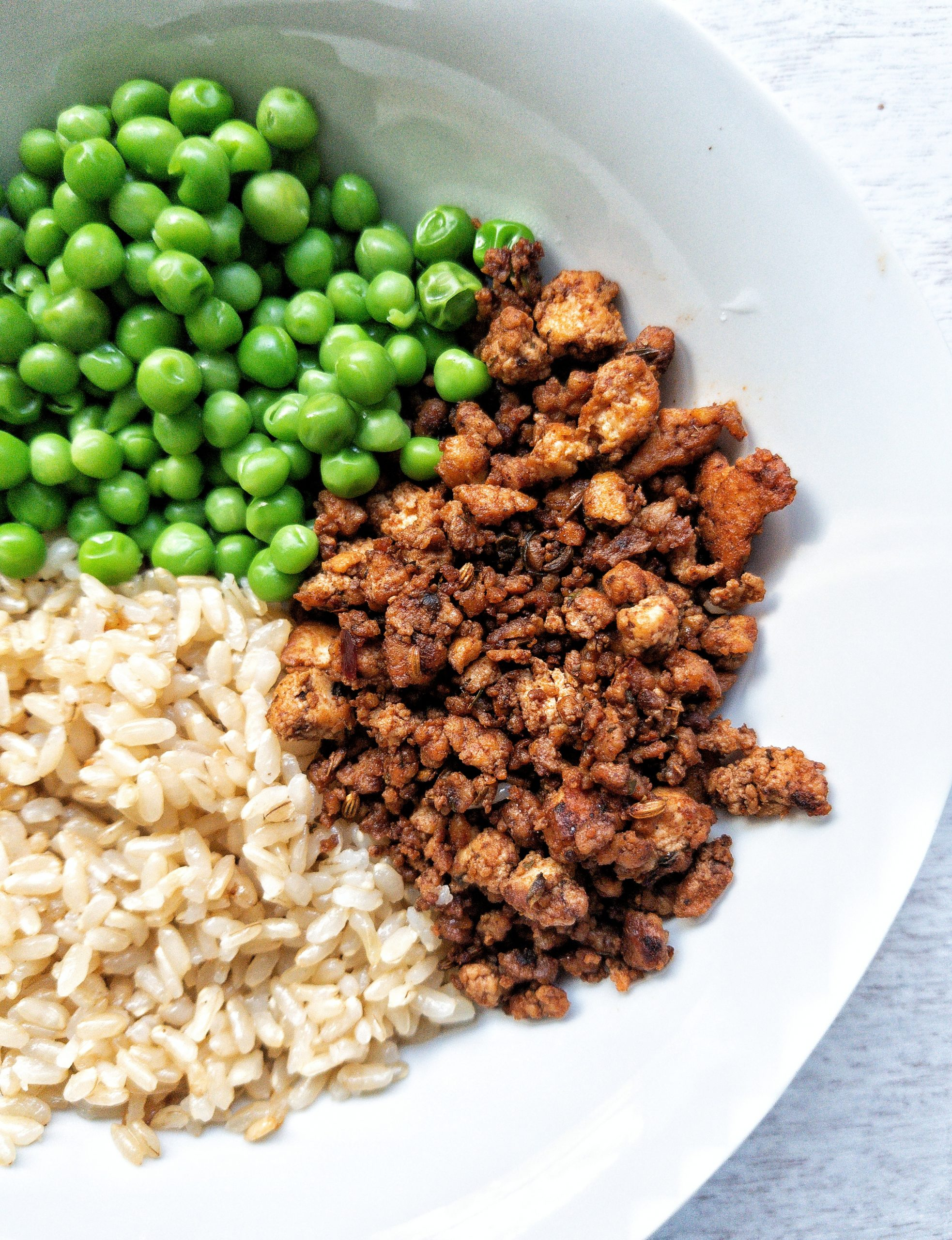Bowl with a side of tofu sausage crumble, green peas, and brown rice