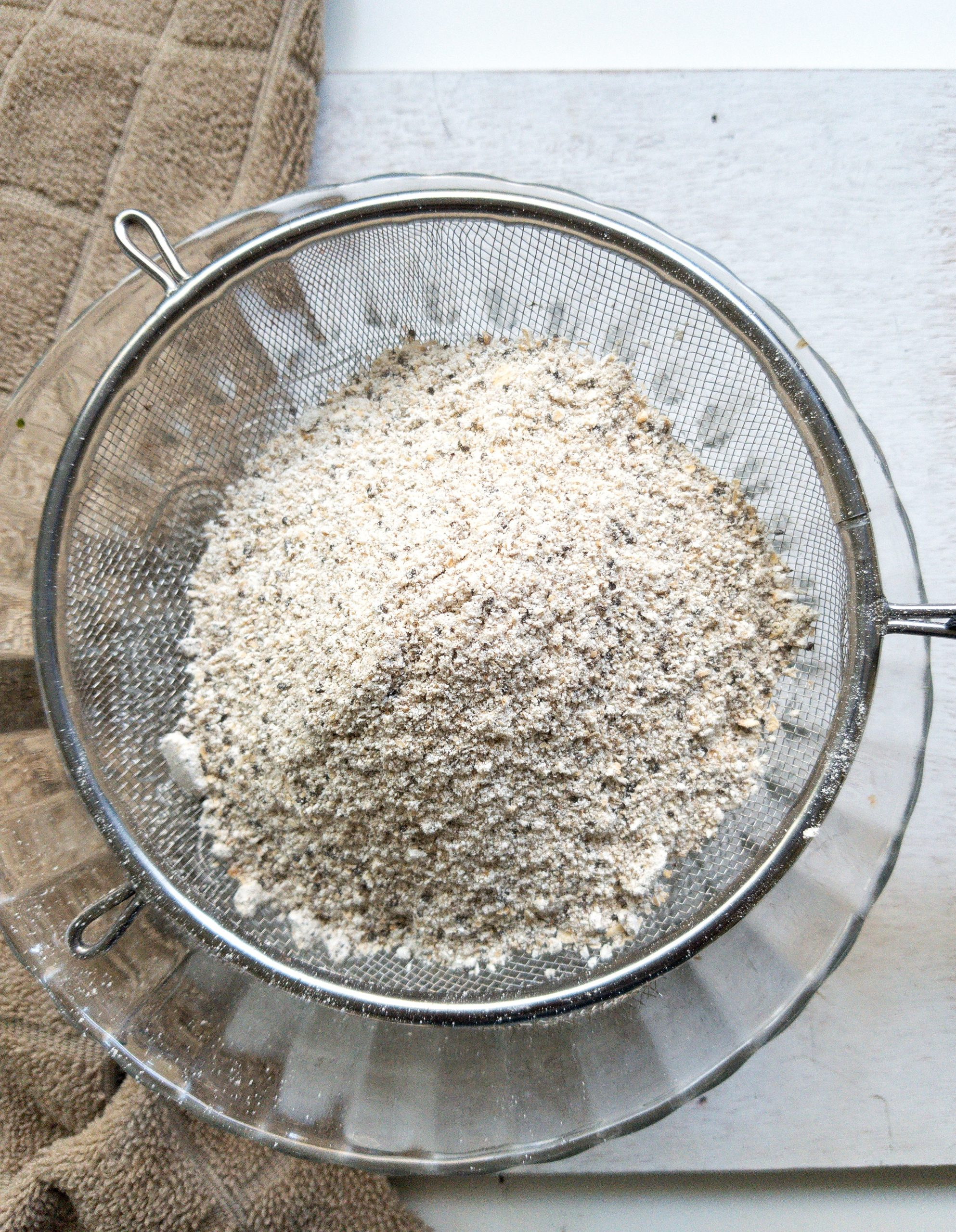 Oat flour sifting over a mixing bowl