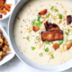 Creamy garlic potato soup in a gray bowl topped with veggie bacon, sliced green onion, and toasted corn