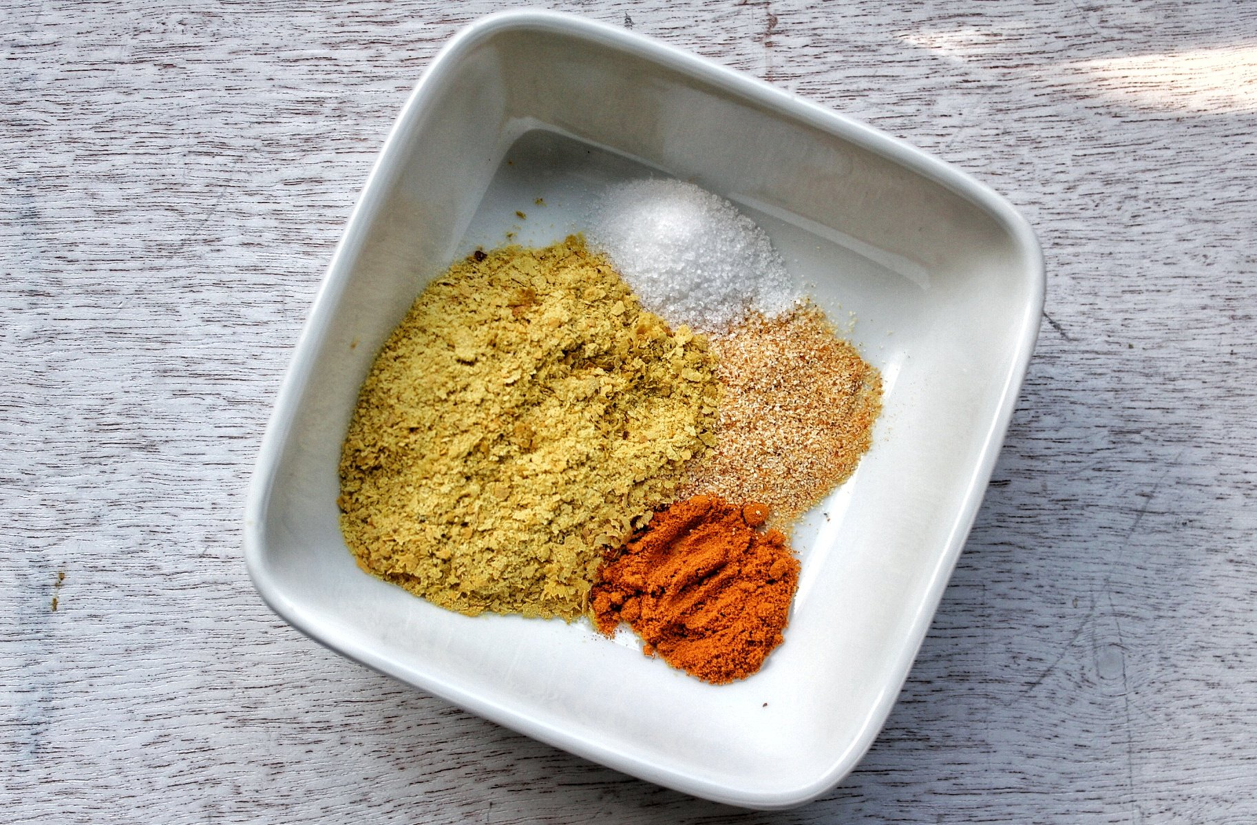 Nutritional yeast, salt, garlic powder, and turmeric in a small white glass bowl