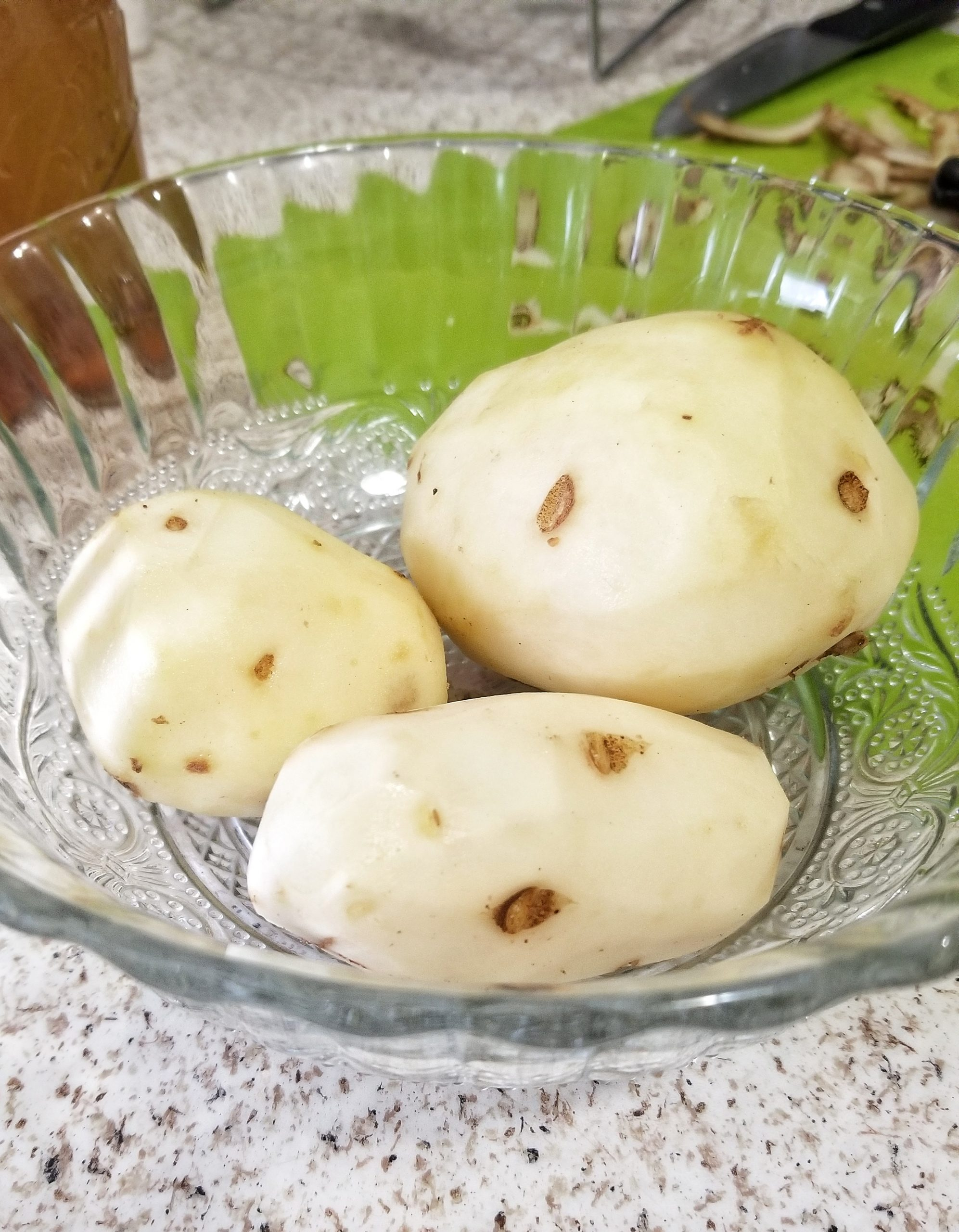 Three peeled russet potatoes in a bowl