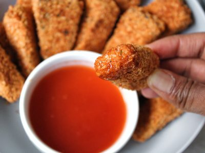 Close up extra crispy nuggets with a honey hot sauce