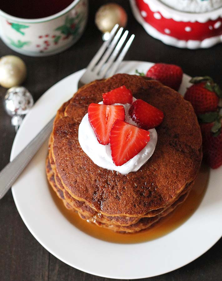 Stack of gingerbread pancakes topped with sliced strawberries