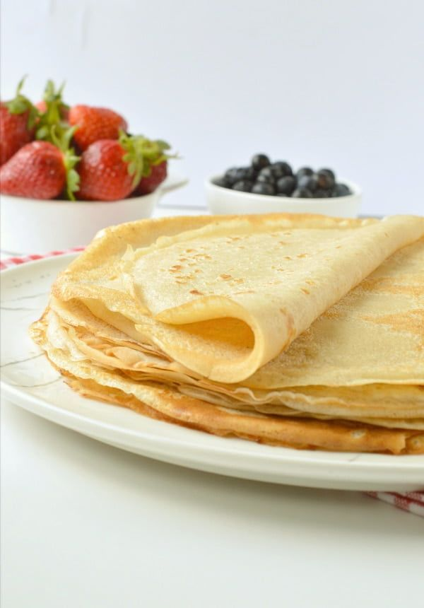 Folded crepes with a side of fruit
