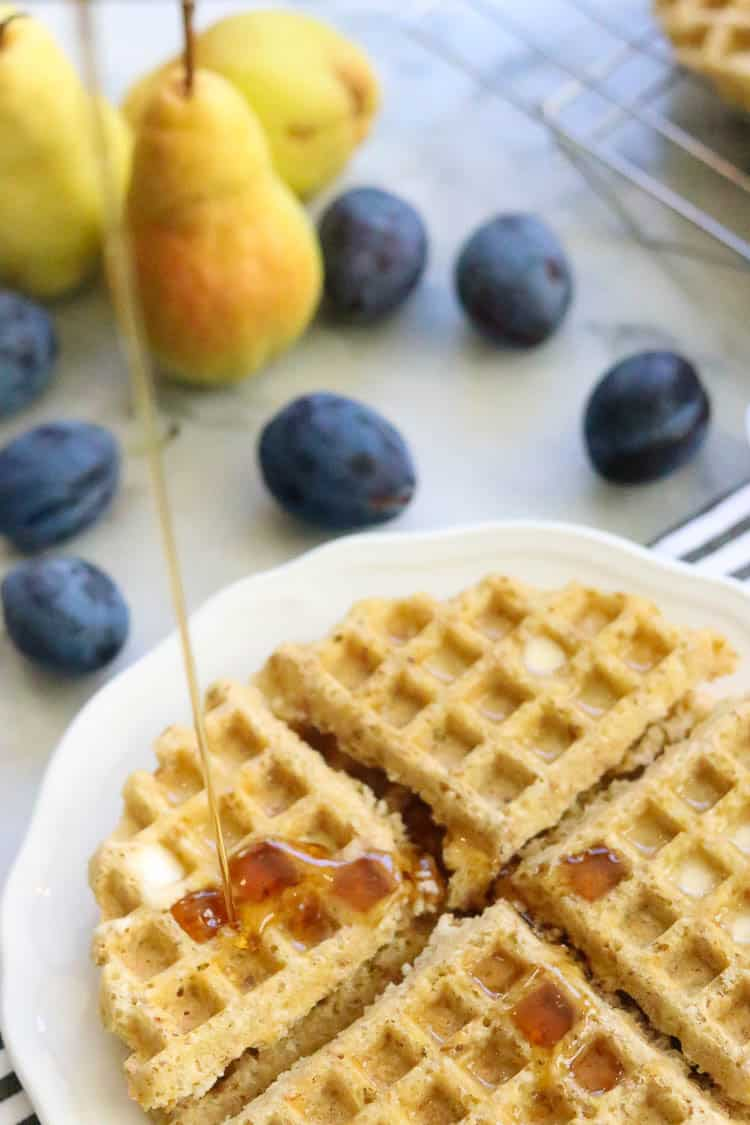 Gluten free waffles with a pour of maple syrup