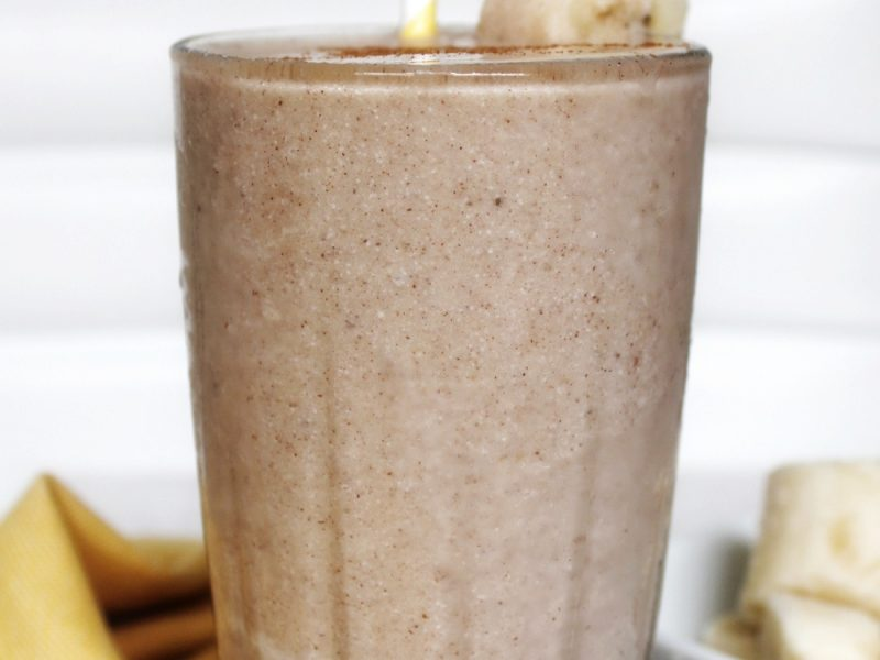 Milkshake in a glass cup with sliced banana and a yellow white stripped straw
