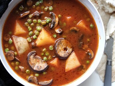 Vegetable soup with mushroom, potatoes, and peas