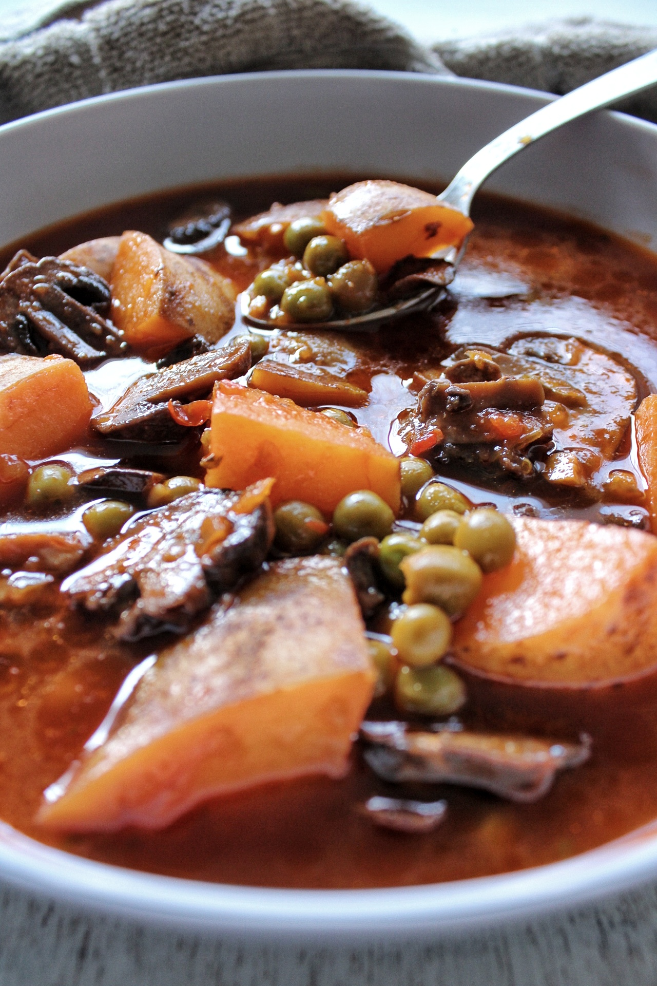 Soup close-up with potatoes, peas, and mushrooms