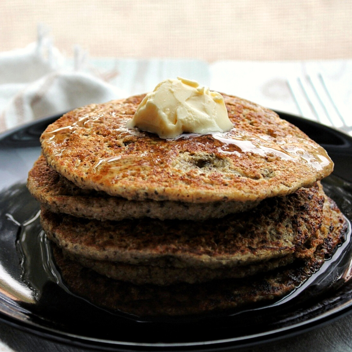 Stack of gluten-free oat bran pancakes topped with vegan butter and syrup.