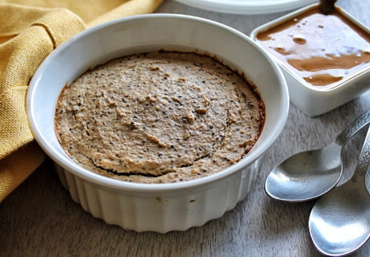Baked oats in a oven-safe bowl with a side of natural peanut butter