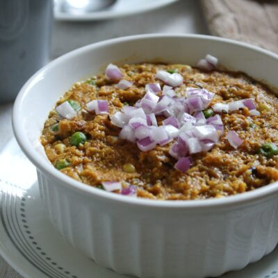 Bowl of vegan, creamy savory oatmeal with Indian spices and flavors.