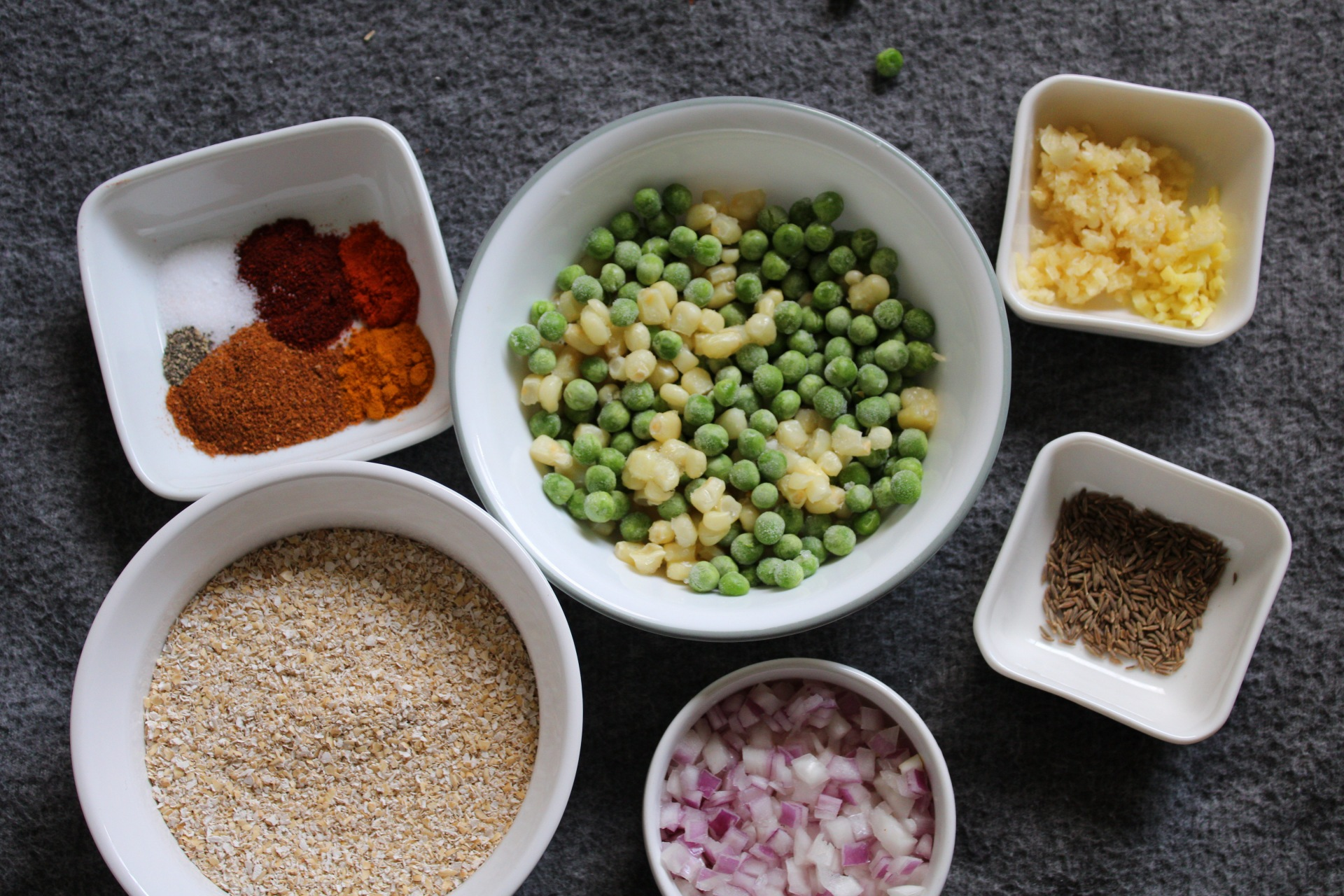 Frozen peas, frozen corn, garlic, cumin, onion, oats, and spices in small bowls