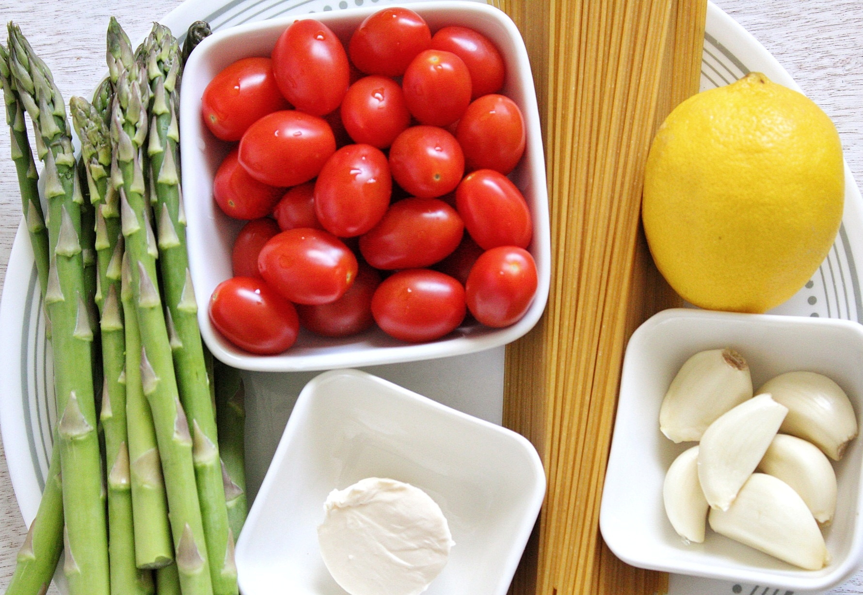 Uncooked spaghetti, whole lemon, garlic cloves, vegan butter, asparagus, and tomatoes on a plate