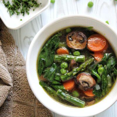 Springtime soup with mushrooms, asparagus, peas, and carrots