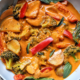 Thai-style vegetable curry in a bowl made with red bell peppers, potatoes, and broccoli.