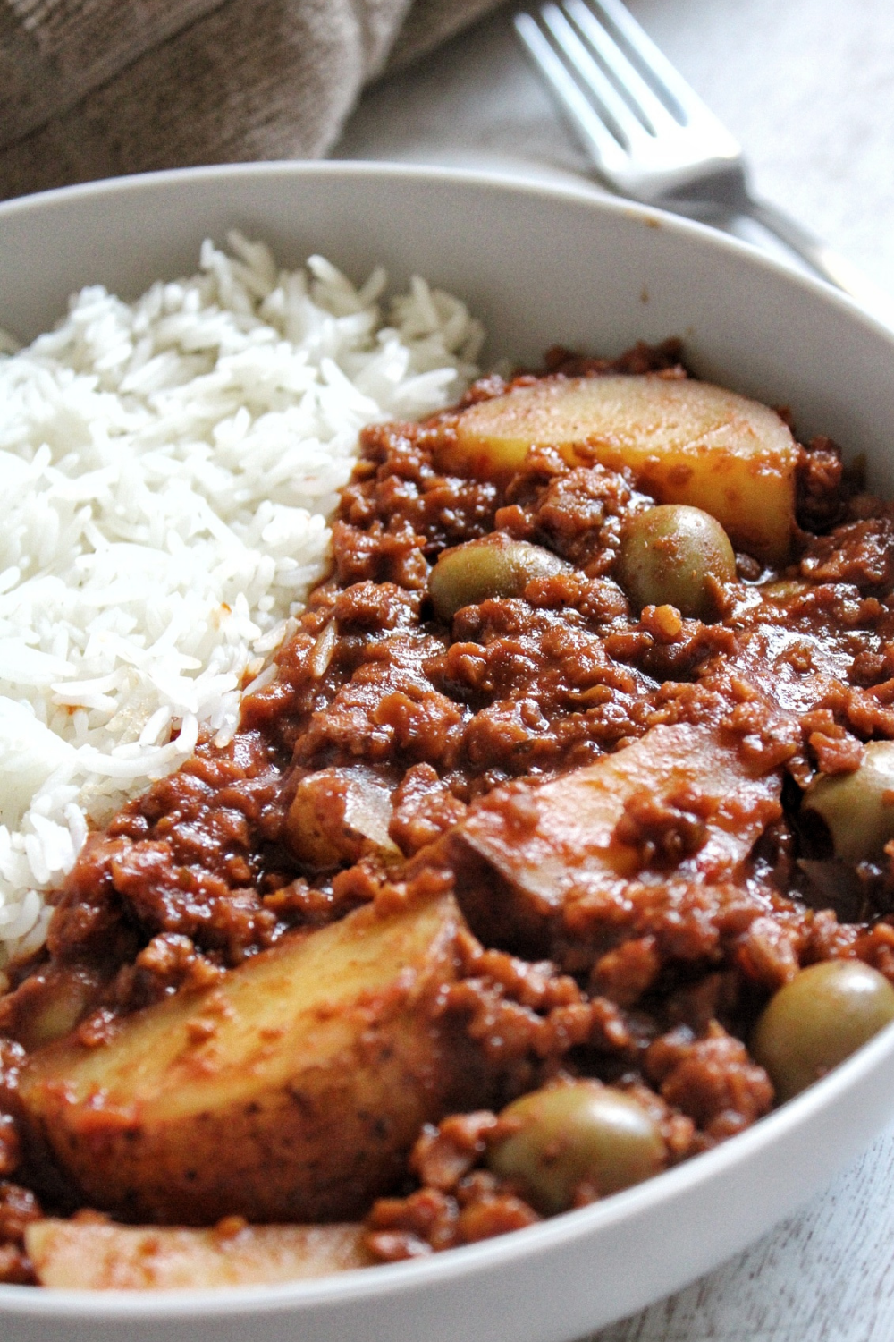 Vegan picadillo with potatoes and green Spanish olives with a side of white rice.