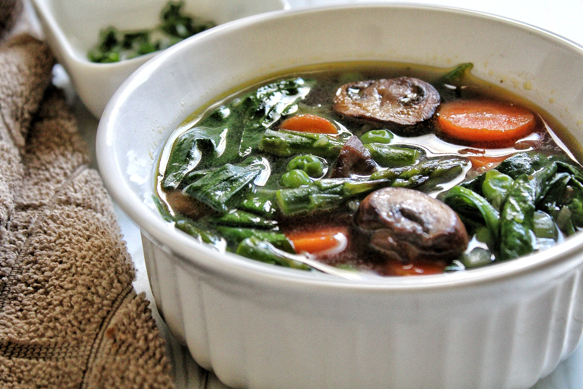 Spring soup with sliced carrots, mushroom, asparagus, and spinach in a bowl