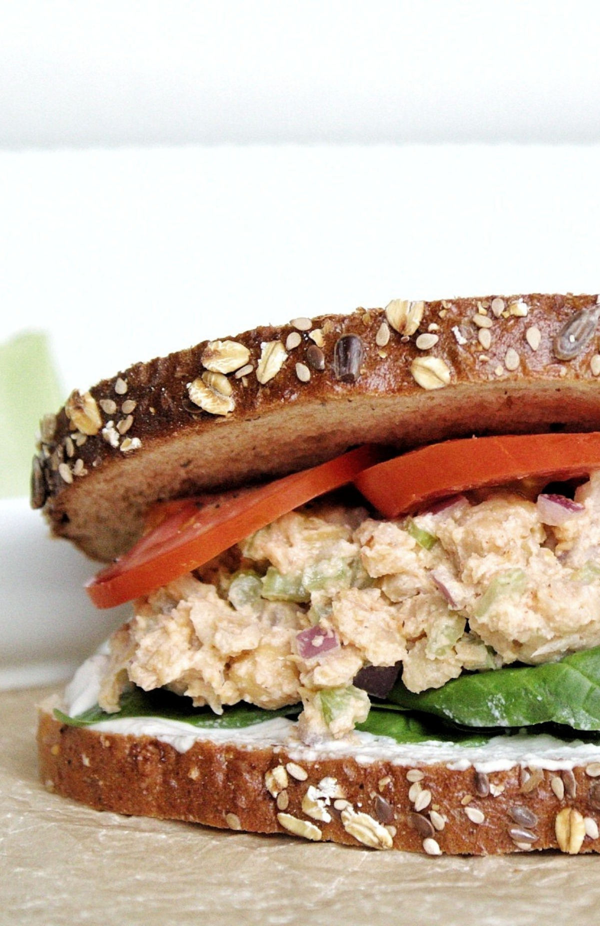 Closeup of chickpea salad sandwich with spinach, cashew cream, and sliced tomatoes