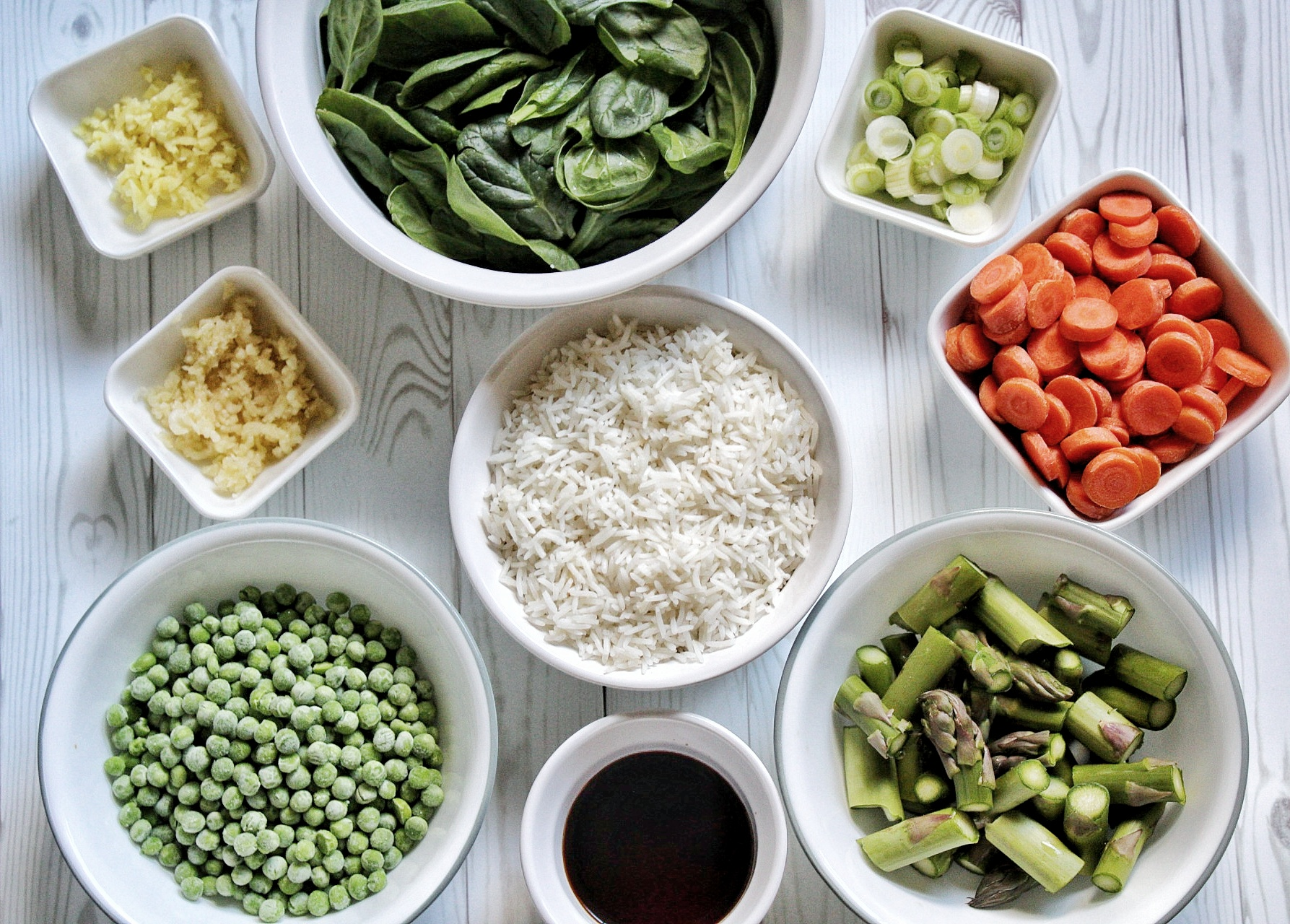 Spinach, green onions, carrots, asparagus, soy sauce, rice, green peas, garlic, and ginger in small bowls