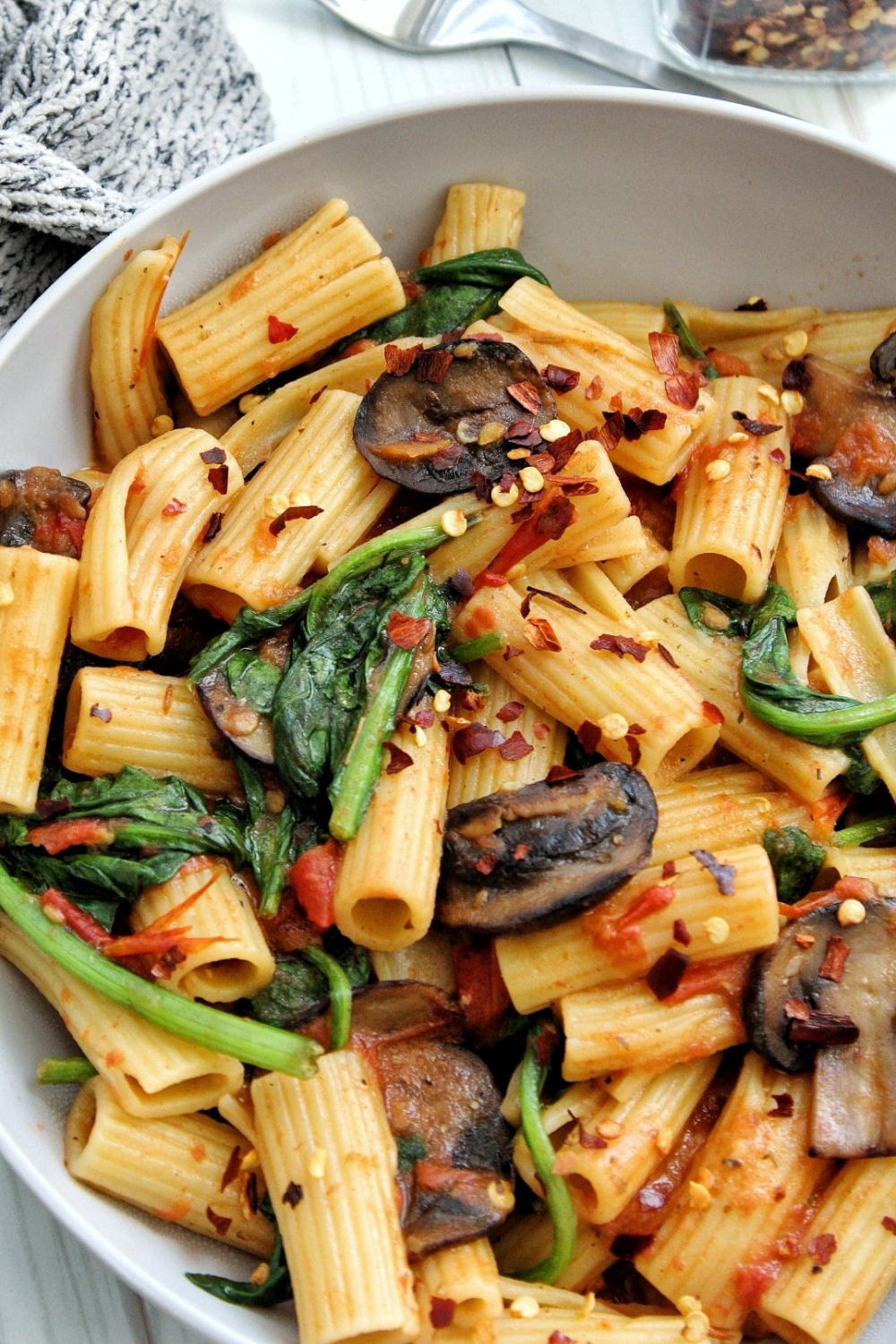Closeup rigatoni pasta with mushrooms, spinach, and red chili flakes