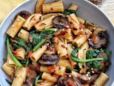 One-pot rigatoni pasta in a bowl with mushrooms, spinach, red chili flakes