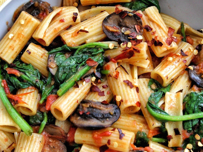 One-pot rigatoni pasta in a bowl with mushrooms, spinach, red chili flakes.