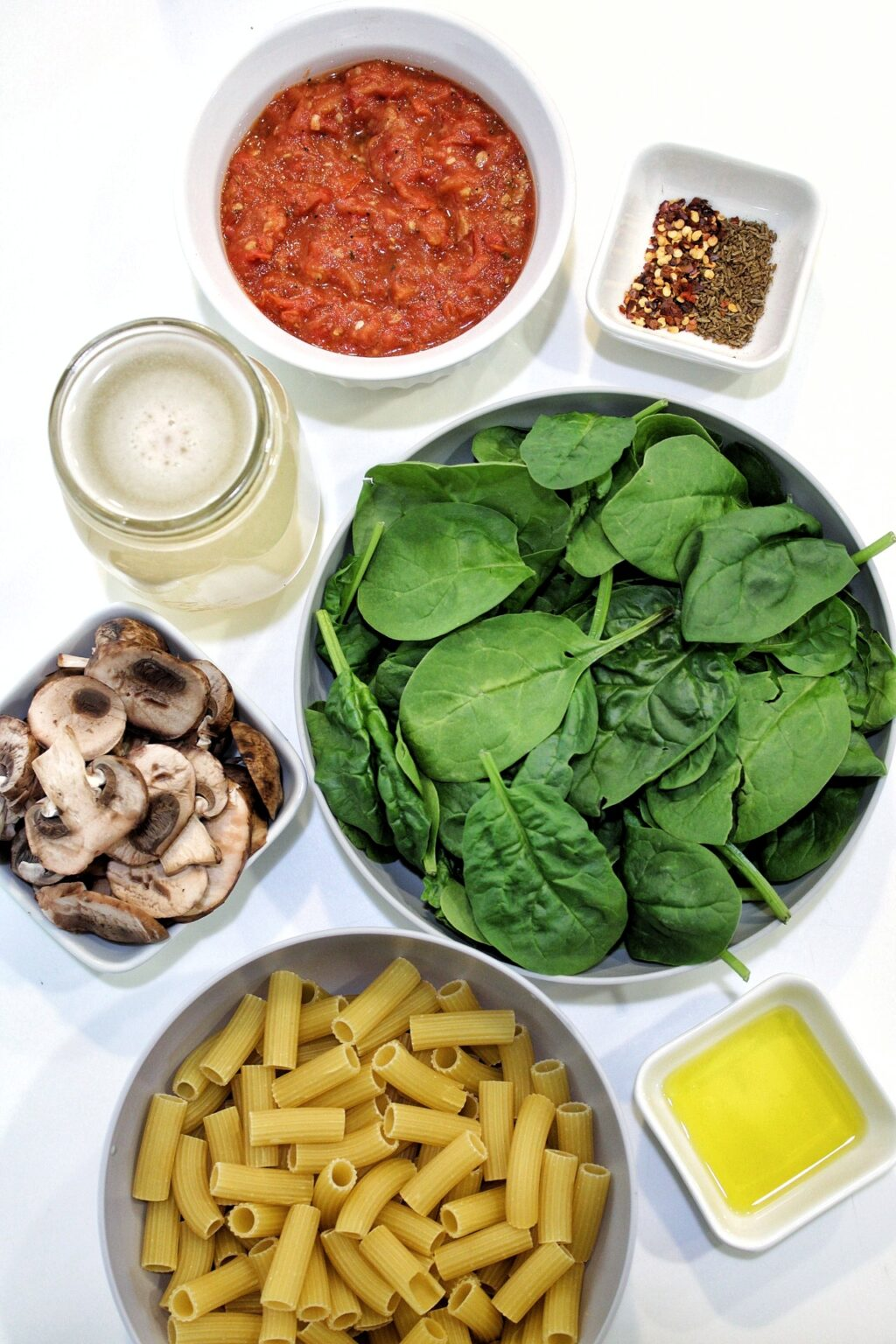 One-pot pasta ingredients: spinach, sliced mushrooms, mushroom broth, rigatoni pasta, olive oil, roasted tomatoes, spices