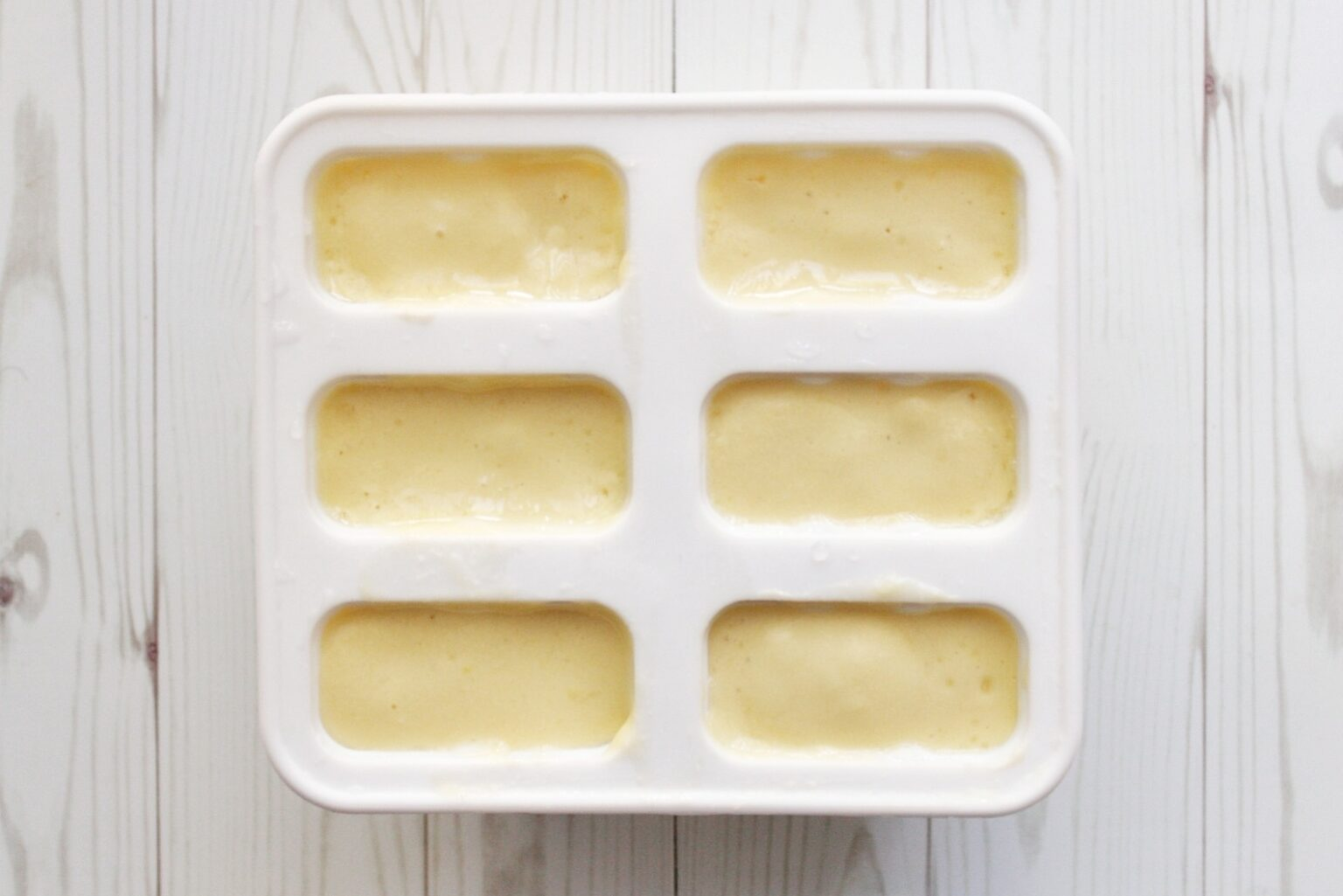 Blended mango, coconut milk, and water in silicone popsicle molds