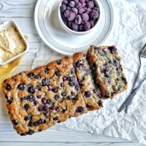Blueberry banana bread with a bowl of frozen berries and vegan butter