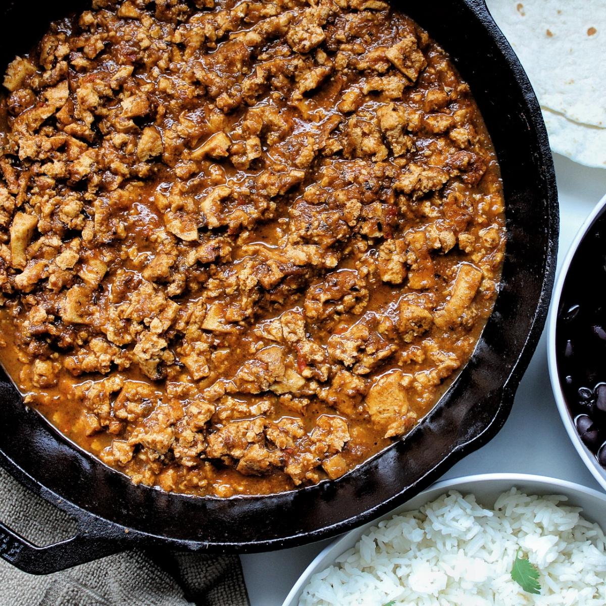 Chipotle-inspired sofritas in a cast-iron pan with a side of rice, beans, and tortillas