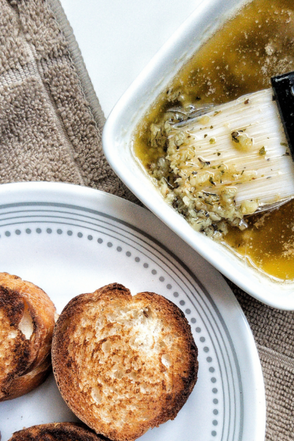 Small round toasts with a side of garlic butter in a small bowl