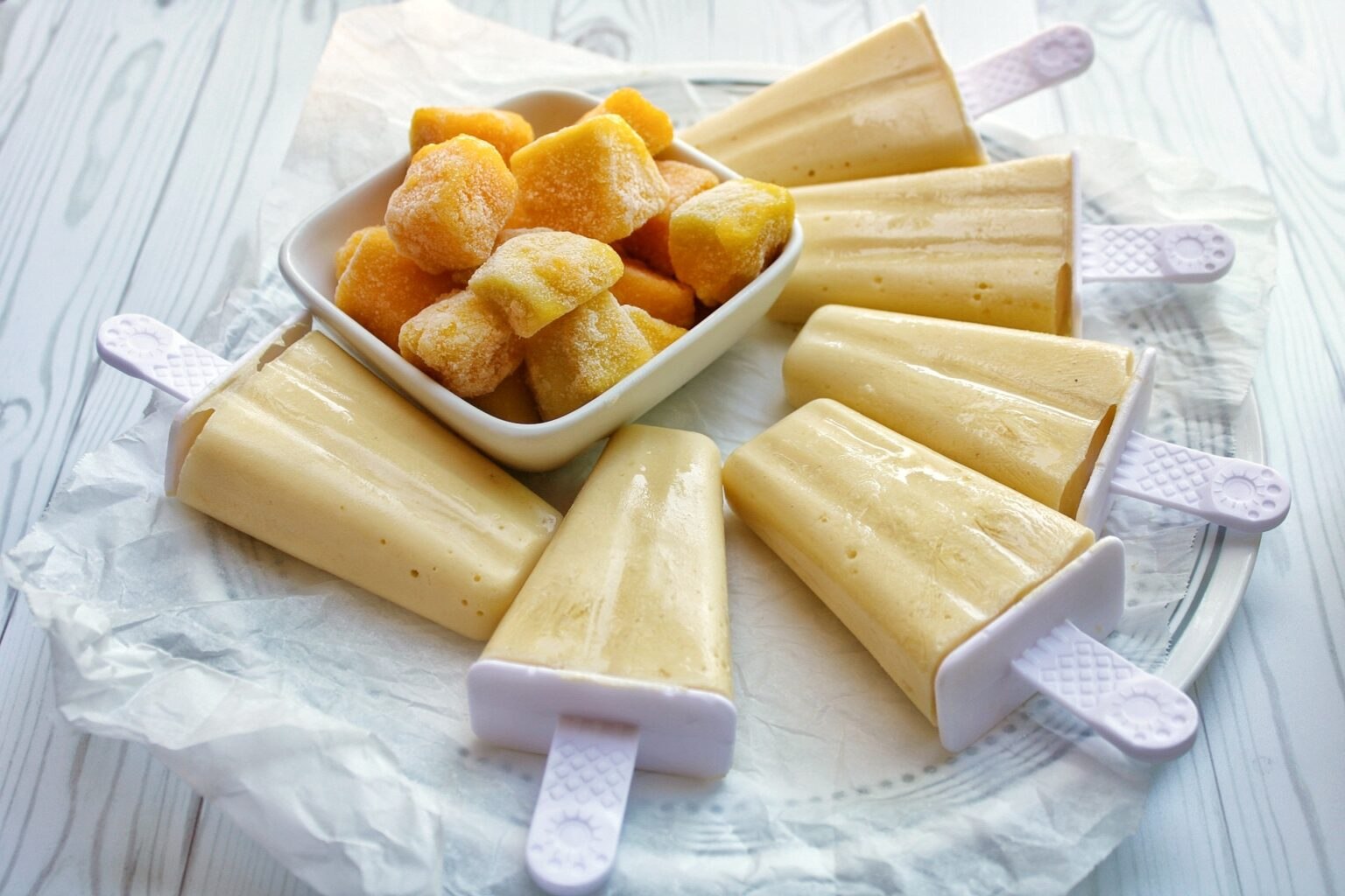 Six mango coconut popsicles on a plate with frozen mango in a bowl