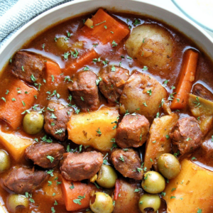 Vegetarian beef stew with chunks of potatoes, carrots, vegan beef, green olives in a gray bowl
