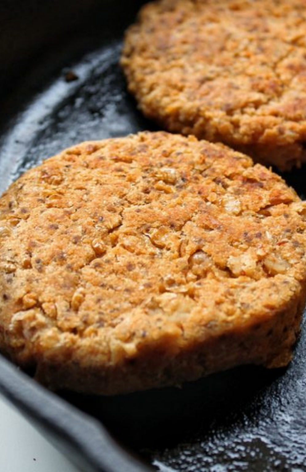 Close up to cannellini burgers in a cast iron skillet.