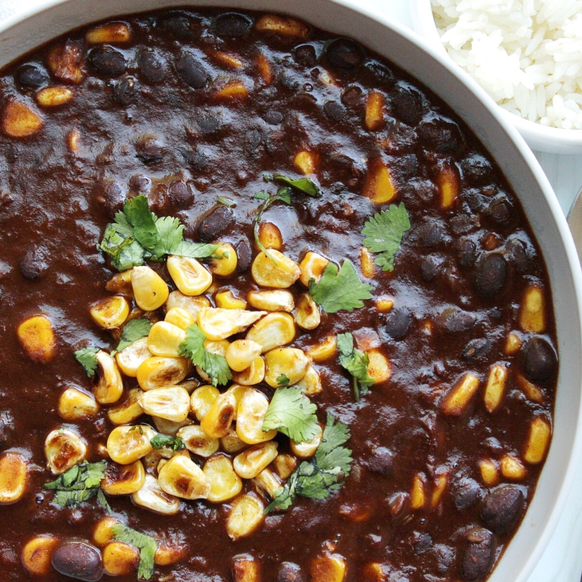 Bowl of vegetarian chili with cilantro and corn.
