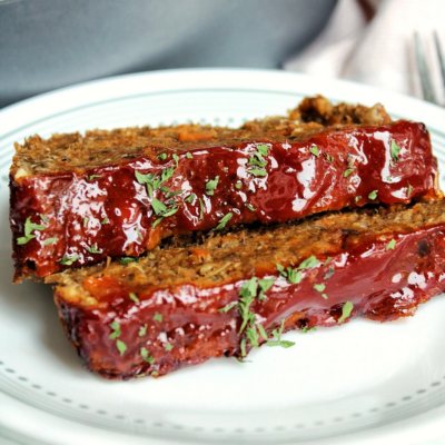 Sliced mushroom lentil loaf with glaze and topped with parsley.