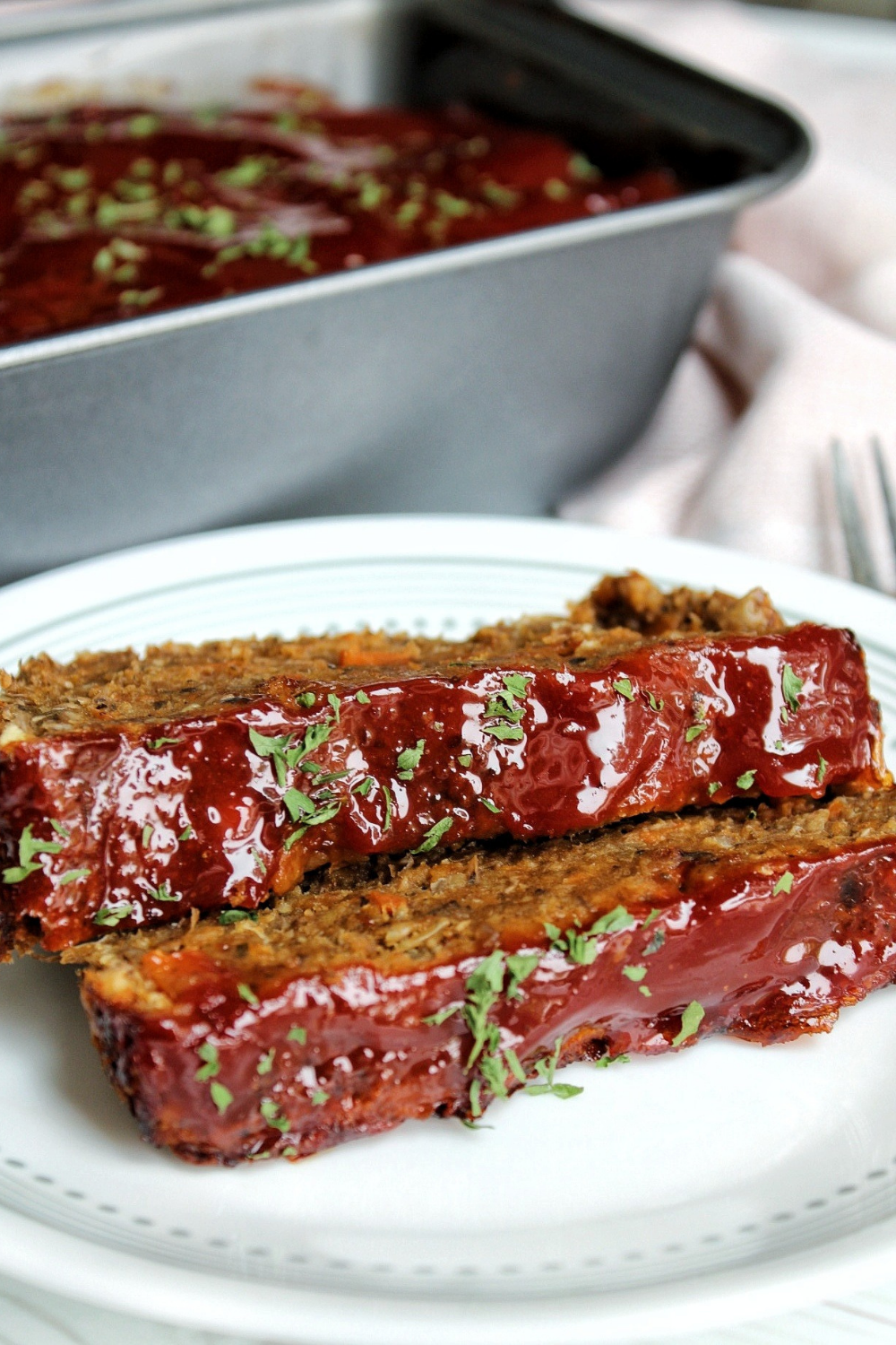 Two slices of vegan lentil loaf with ketchup glaze and topped with parsley.