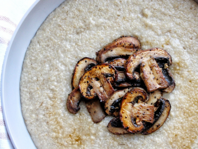 Creamy oat bran porridge topped with mushrooms in a gray bowl.