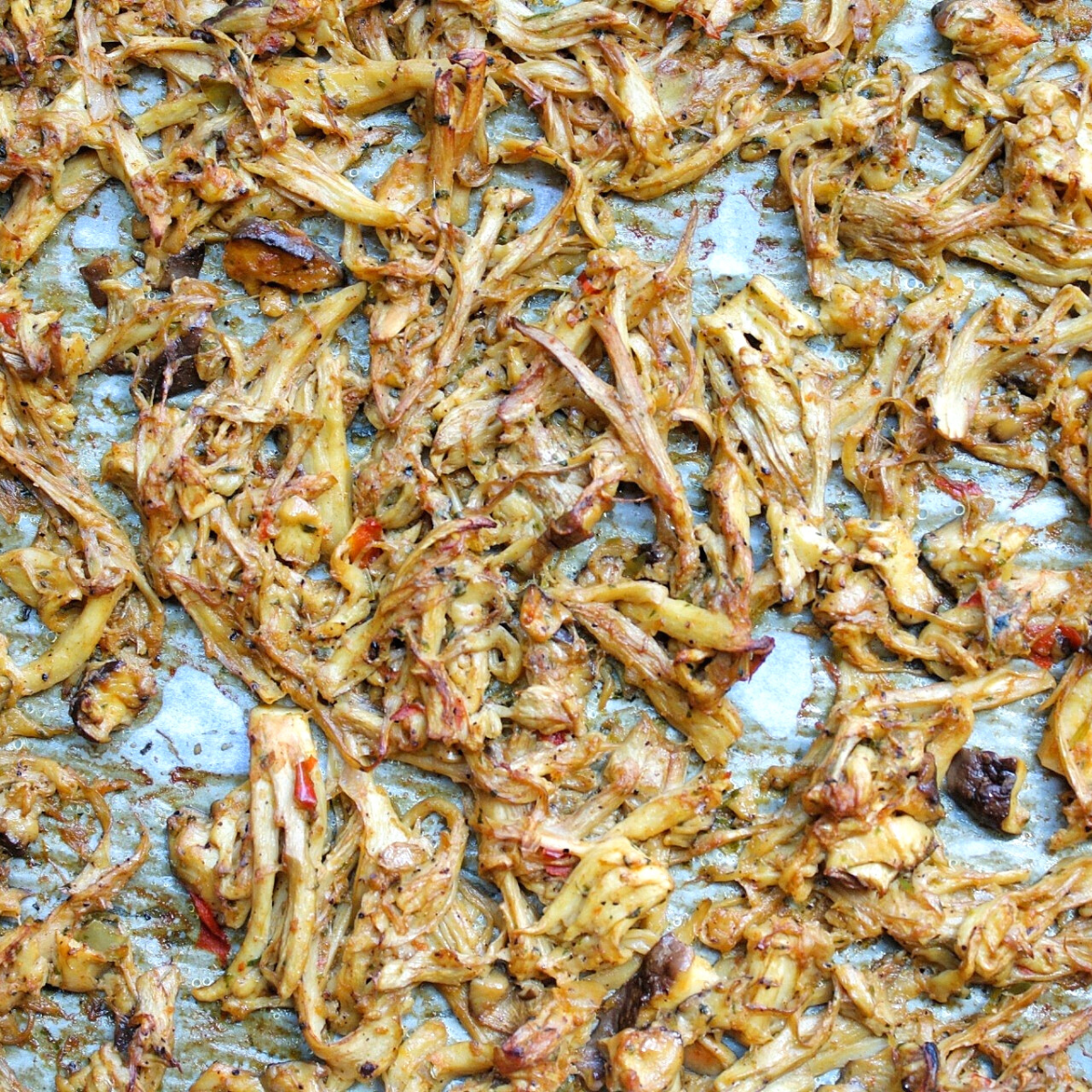 Marinated mushroom shreds on a baking sheet lined with parchment paper.