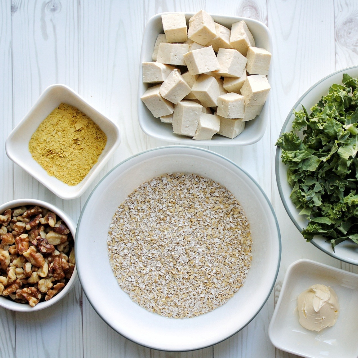 Ingredients for oat bran including cubed tofu, kale, walnuts, oat bran, vegan butter, and nutritional yeast