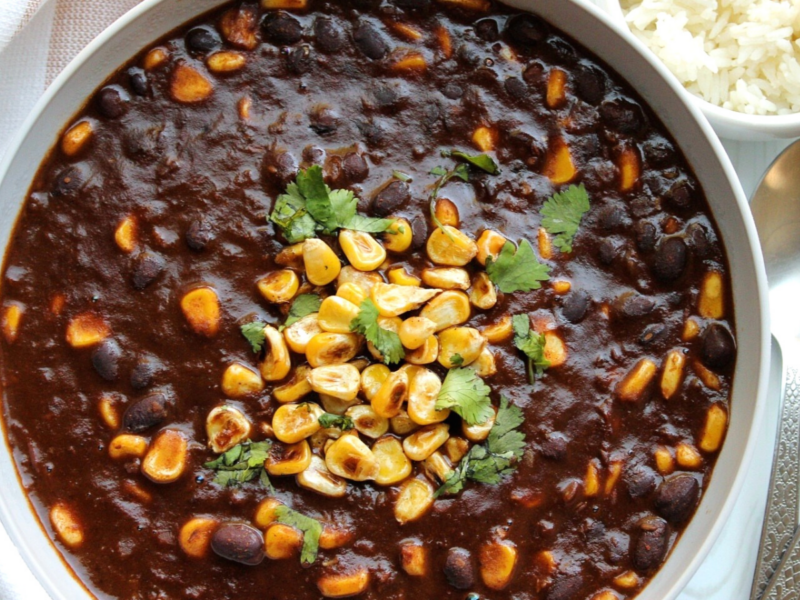 Vegan black bean chili in gray bowl topped with pan-roasted corn and chopped cilantro.