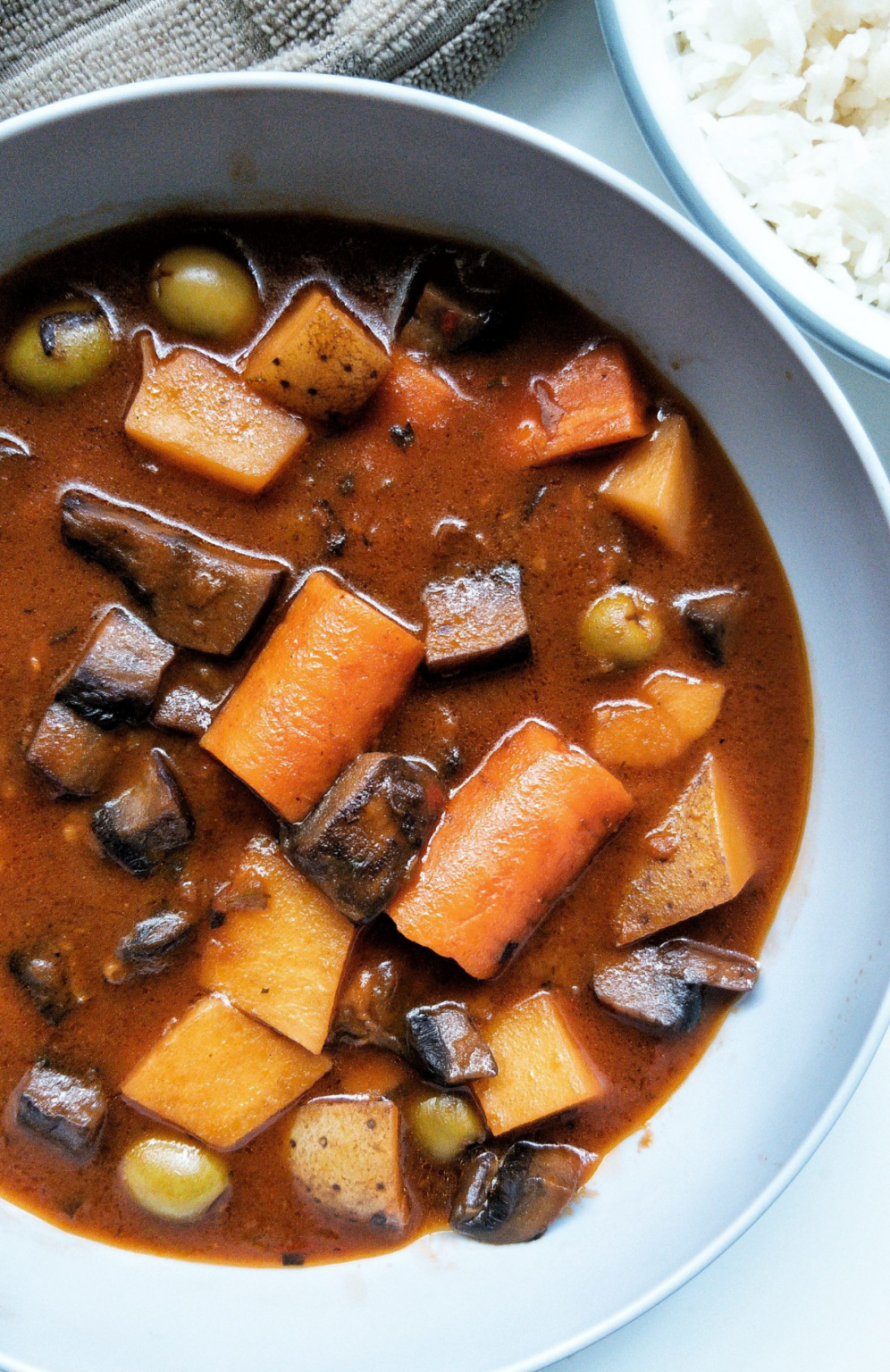 Bowl of plant-based beef stew with mushrooms, carrots, and potatoes.