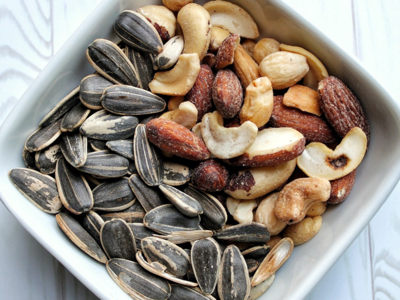 Small white bowl with sunflower seeds and mixed nuts