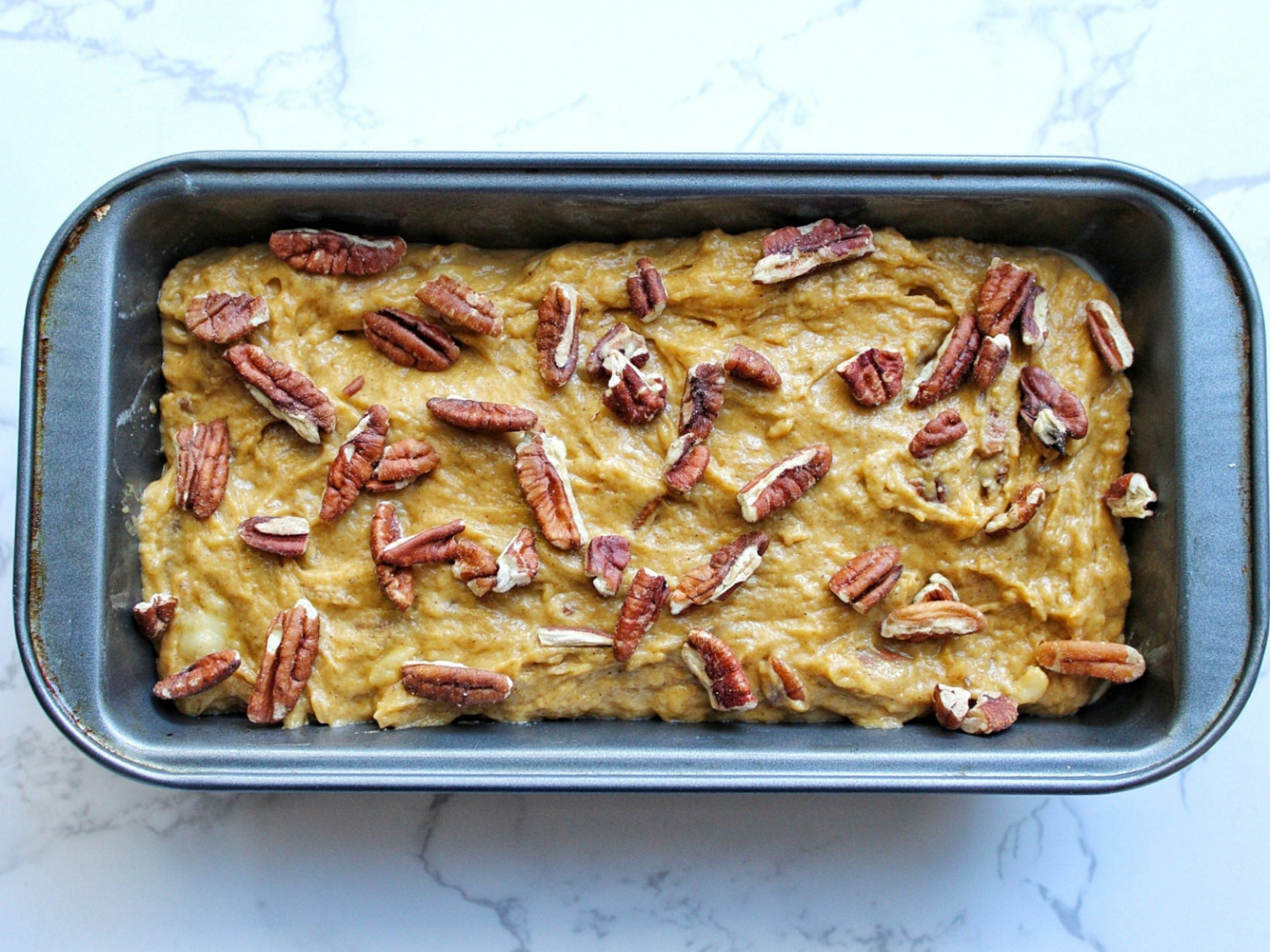 Unbaked or raw sweet cook bread in a loaf pan topped with chopped pecans.