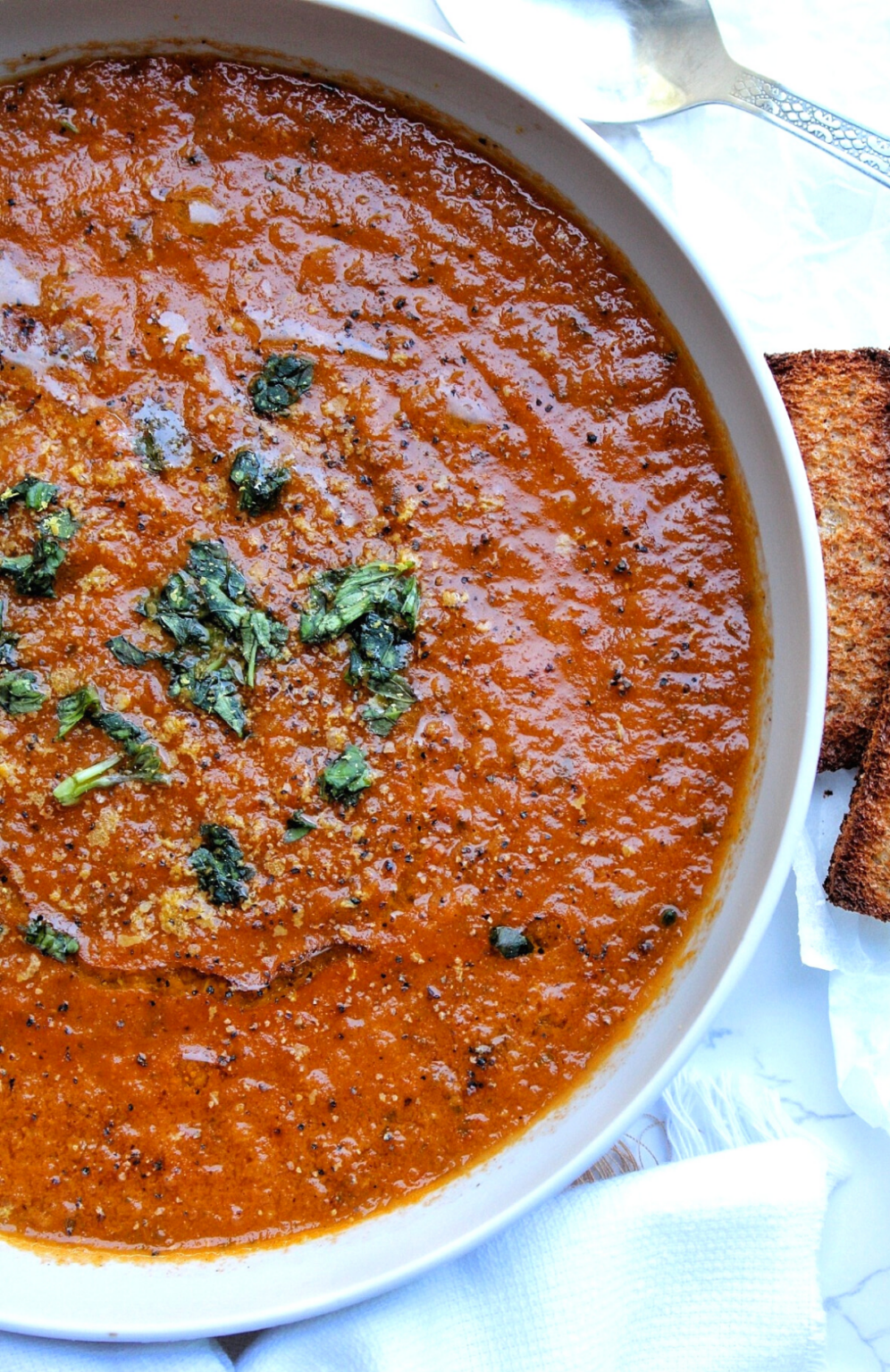 Homemade roasted tomato soup served with choppedbasil and toasted bread.
