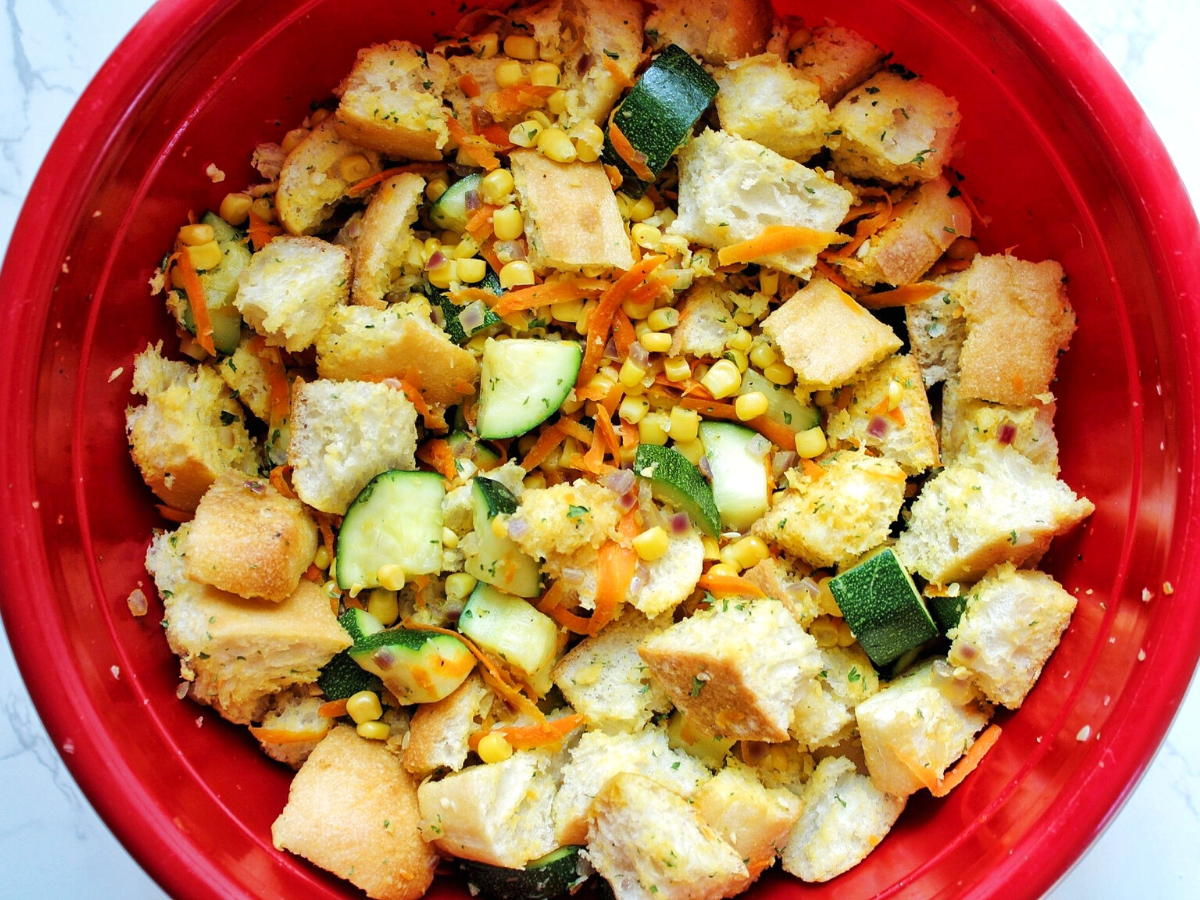 Zucchini stuffing casserole ingredients in a large, red mixing bowl.